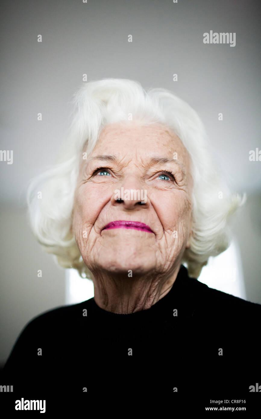 Portrait of senior woman looking up, studio shot Photo Stock