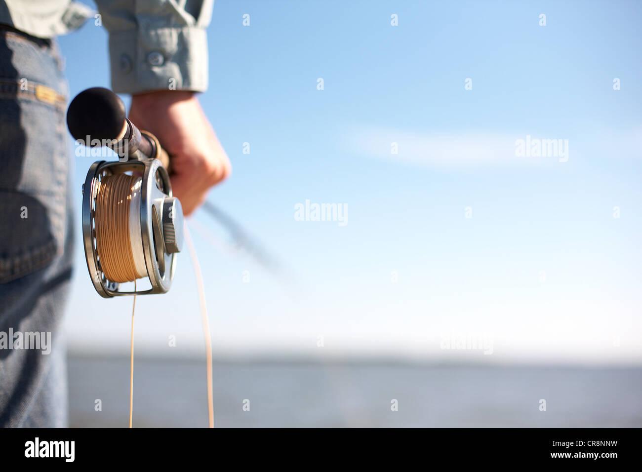 Fisherman holding une canne à mouche Photo Stock