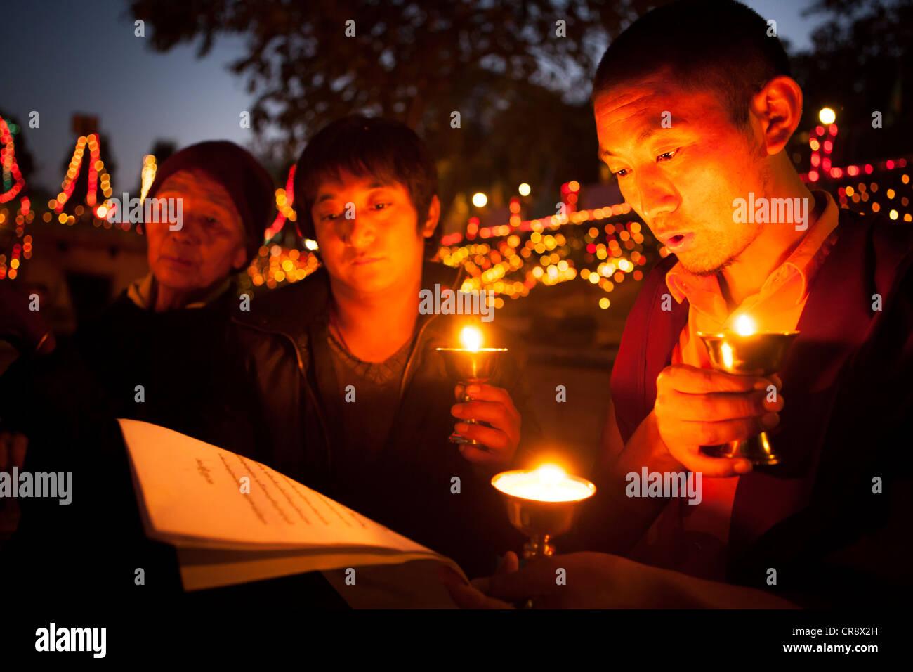 Les moines et les pèlerins prient avec lampe à pétrole le soir , Temple de la Mahabodhi, Bodh Gaya, Photo Stock