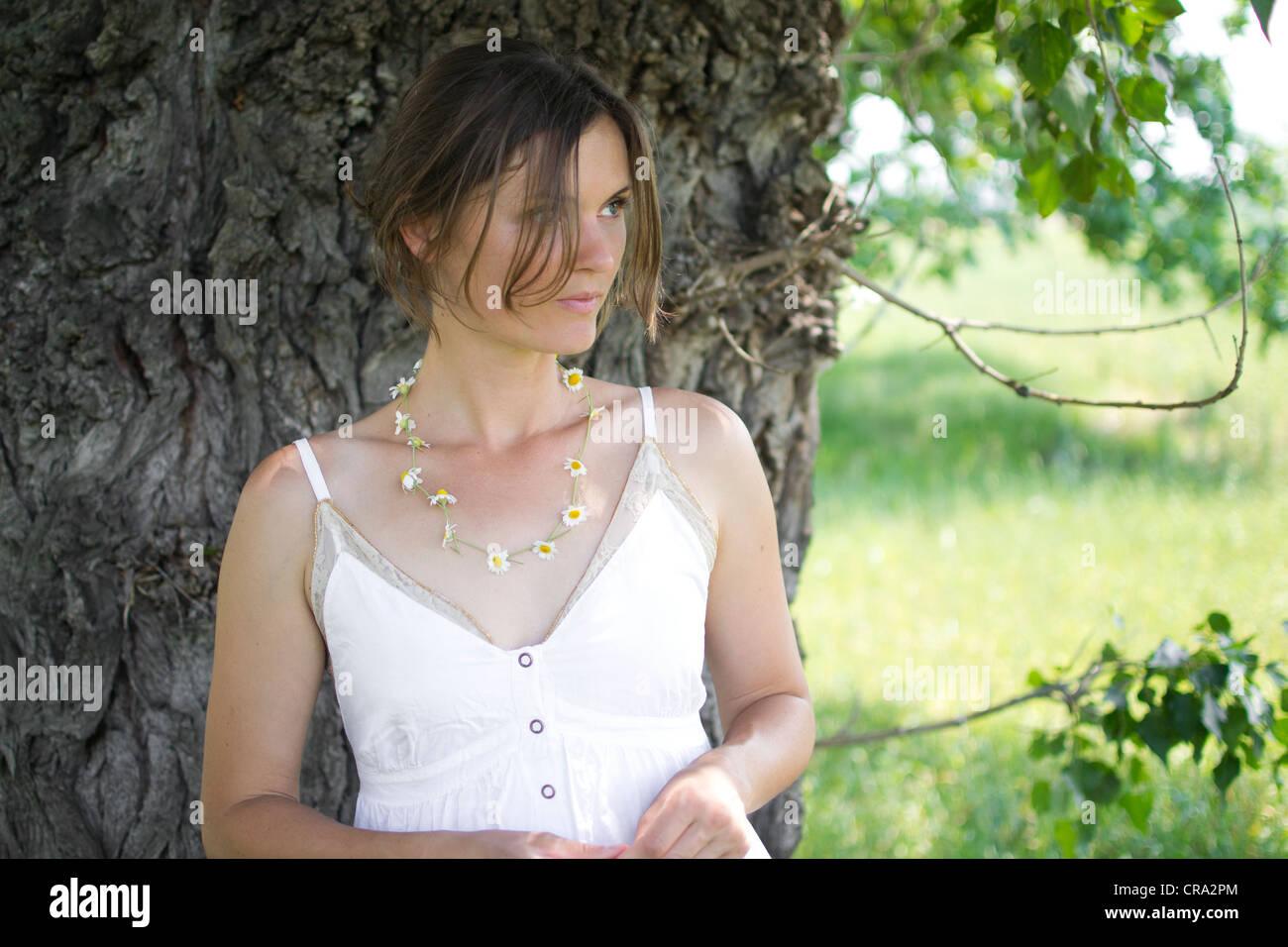 Belle jeune femme de détente dans un pré vert dans la campagne jouant avec un rouge coquelicot Banque D'Images