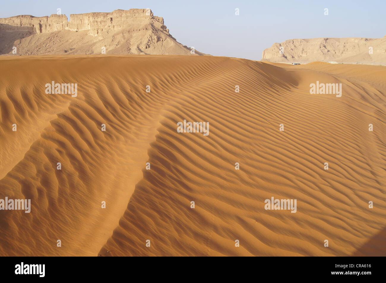 Dunes de sable avec des formations rocheuses en arrière-plan prises sur les Sables rouges, Riyadh, Royaume Photo Stock