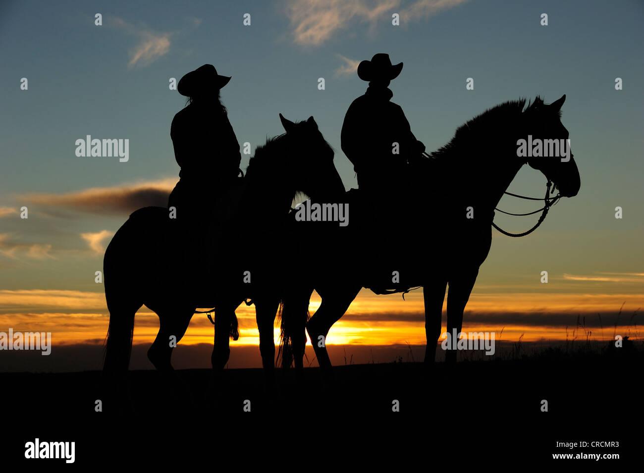 Cowboy et Cowgirl assis à cheval au coucher du soleil, en Saskatchewan, au Canada, en Amérique du Nord Photo Stock