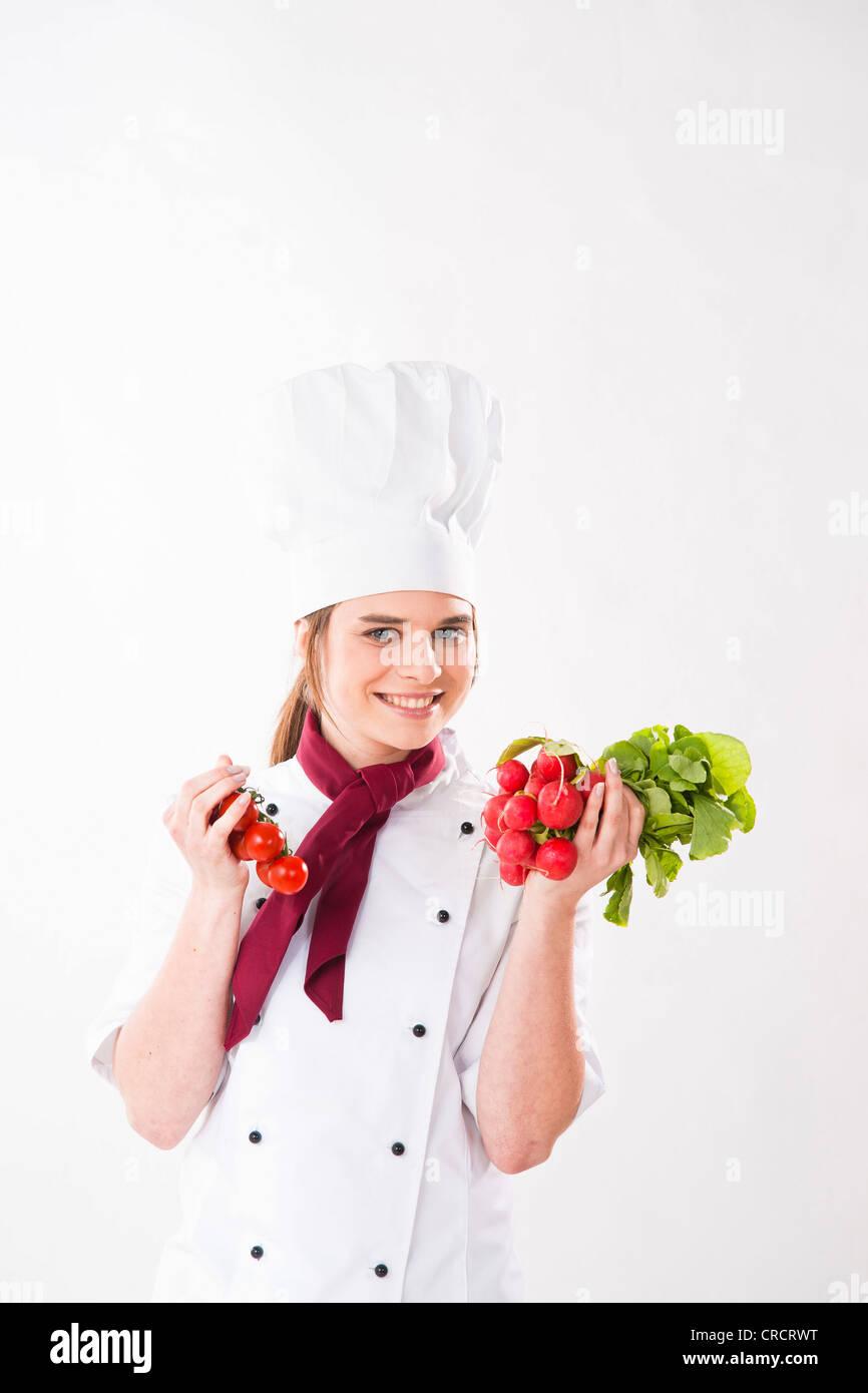 Smilig chef holding le radis et tomates Photo Stock
