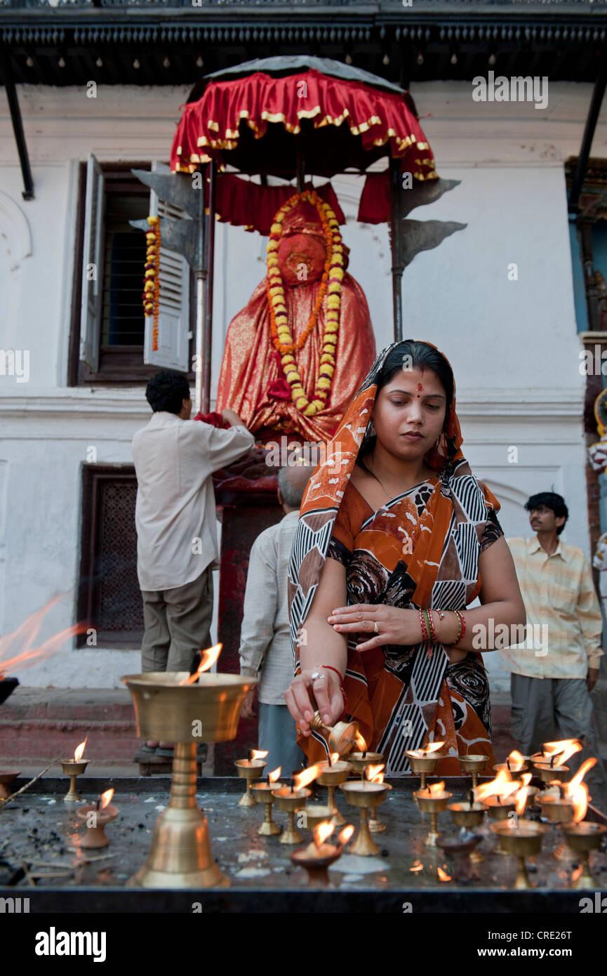 L'hindouisme, les croyants avec lampes à beurre, Hanuman statue, place en face de l'Hanuman Dhoka Durbar Photo Stock