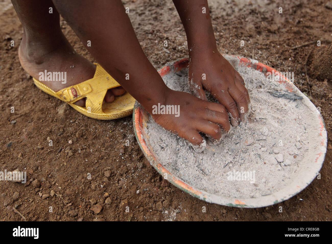 Une fille ramasse une poignée de cendres, un substitut de savon, alors qu'elle se lave les mains à Photo Stock