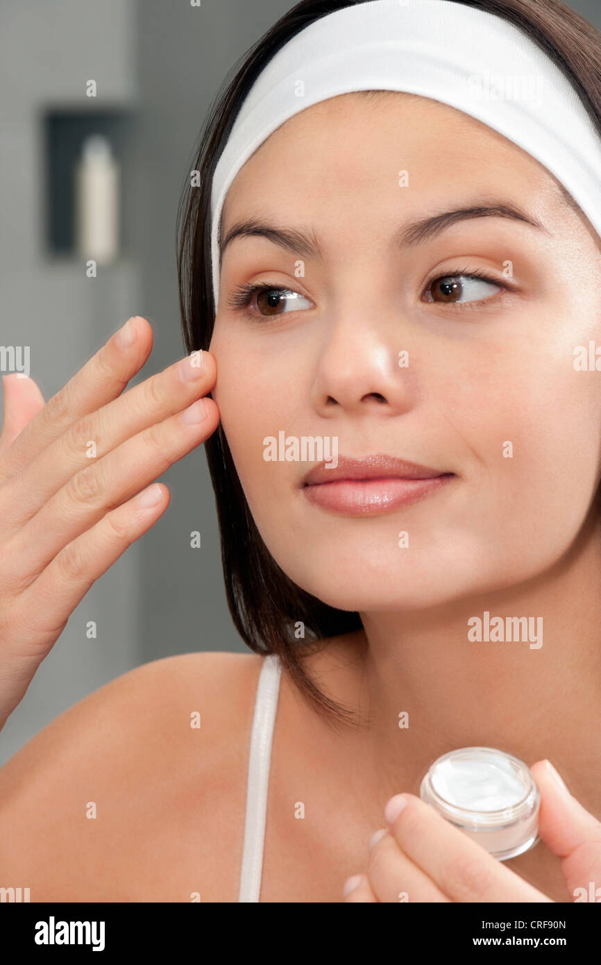Woman applying moisturizer in mirror Photo Stock