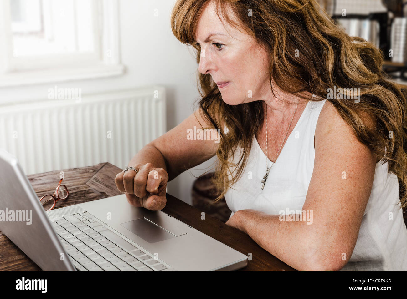 Older woman using laptop in kitchen Photo Stock