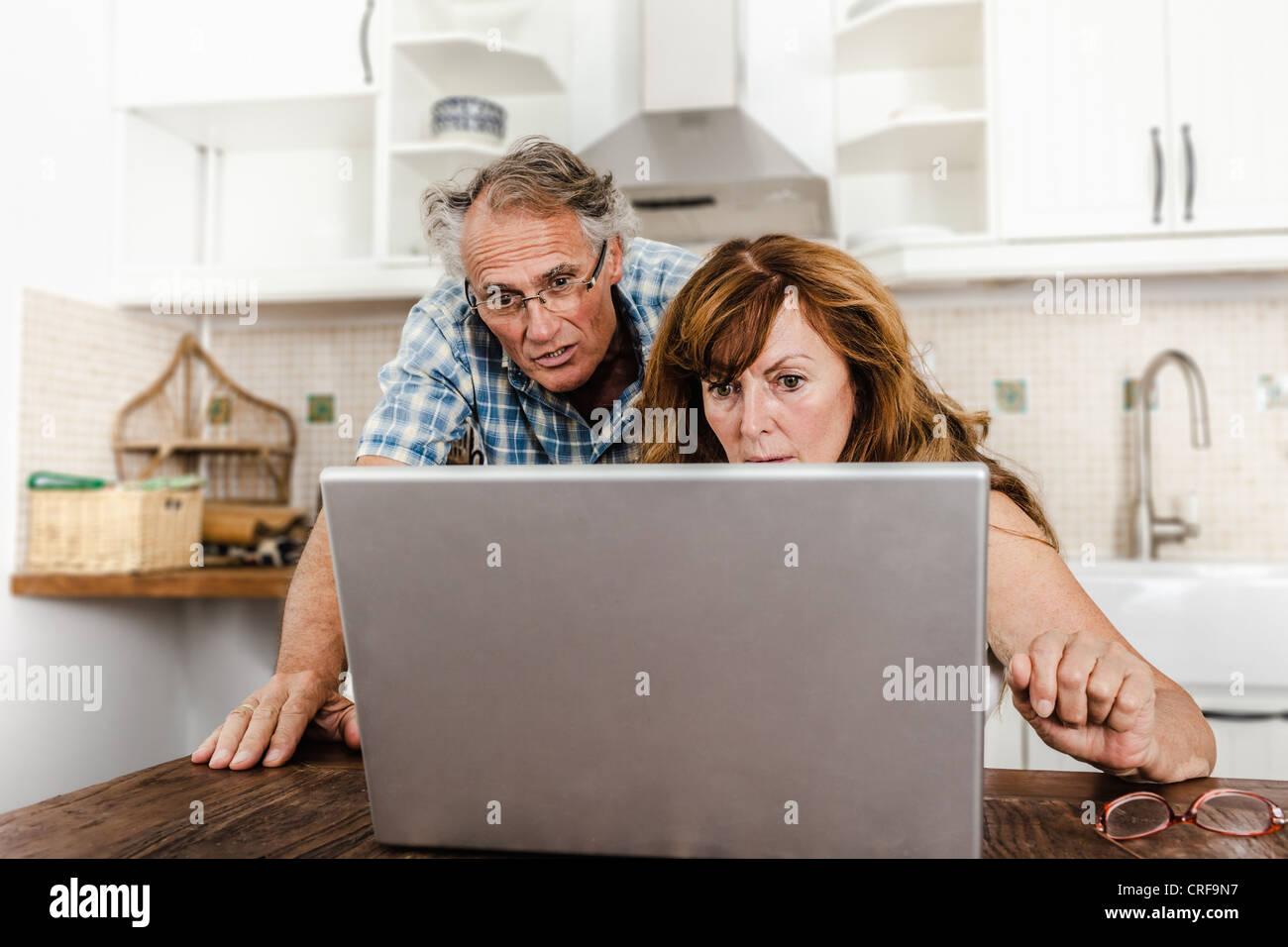 Vieux couple using laptop in kitchen Photo Stock
