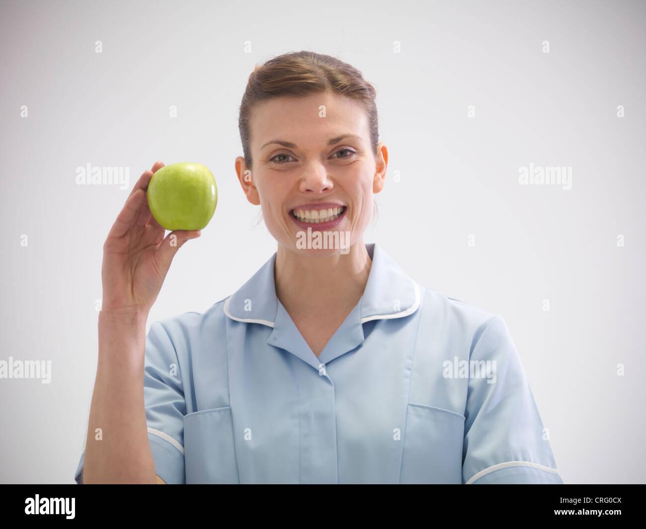 Dentiste Smiling holding apple Photo Stock