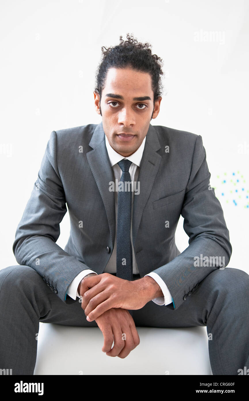 Businessman sitting on pouf Photo Stock