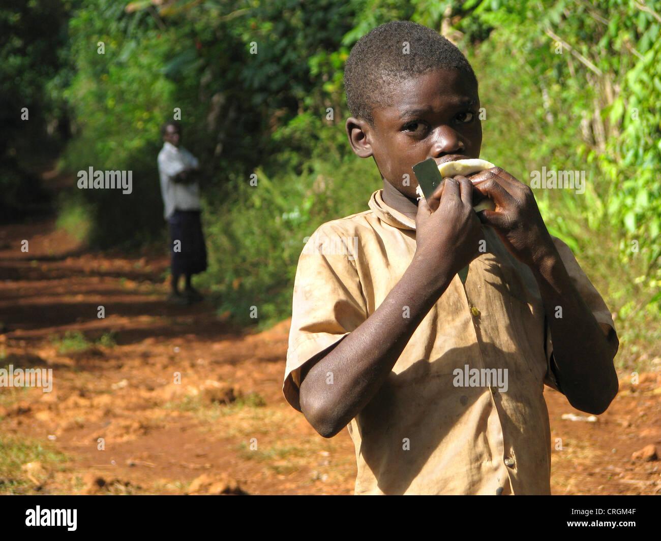 Garçon en zone rurale est de sucer sur une orange, l'homme regarde en arrière-plan, Haïti, Grande Photo Stock