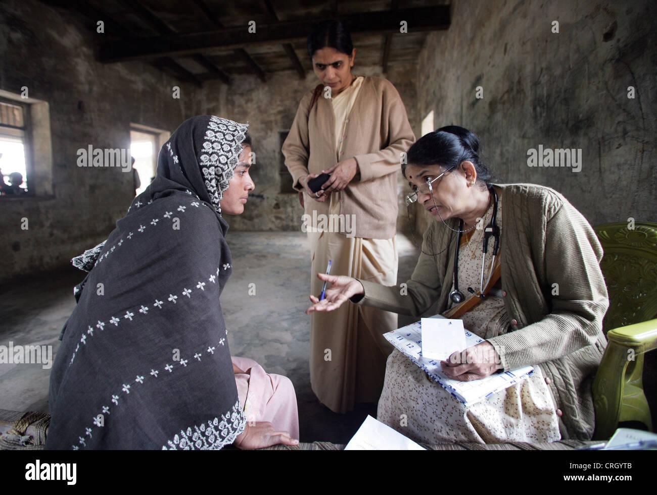 Médecin volontaire (à droite) examine les habitants d'un village en Inde sans aucun frais/image Photo Stock