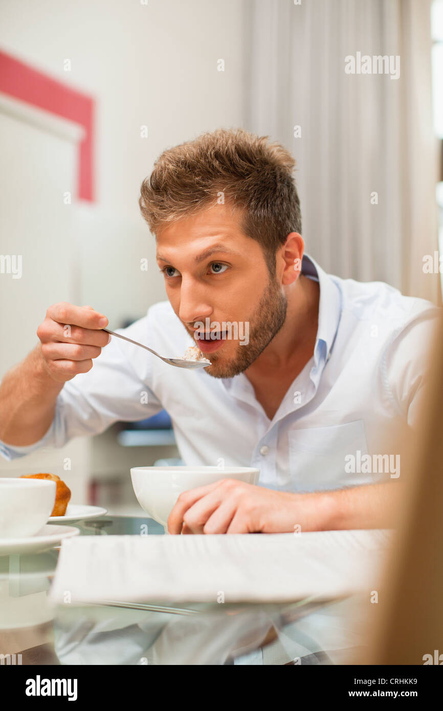 Man eating breakfast at table Photo Stock