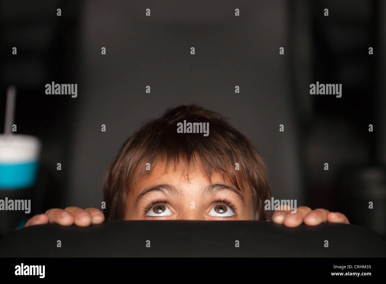 Boy peeking au dessus du siège au cours du film d'horreur dans le théâtre Banque D'Images