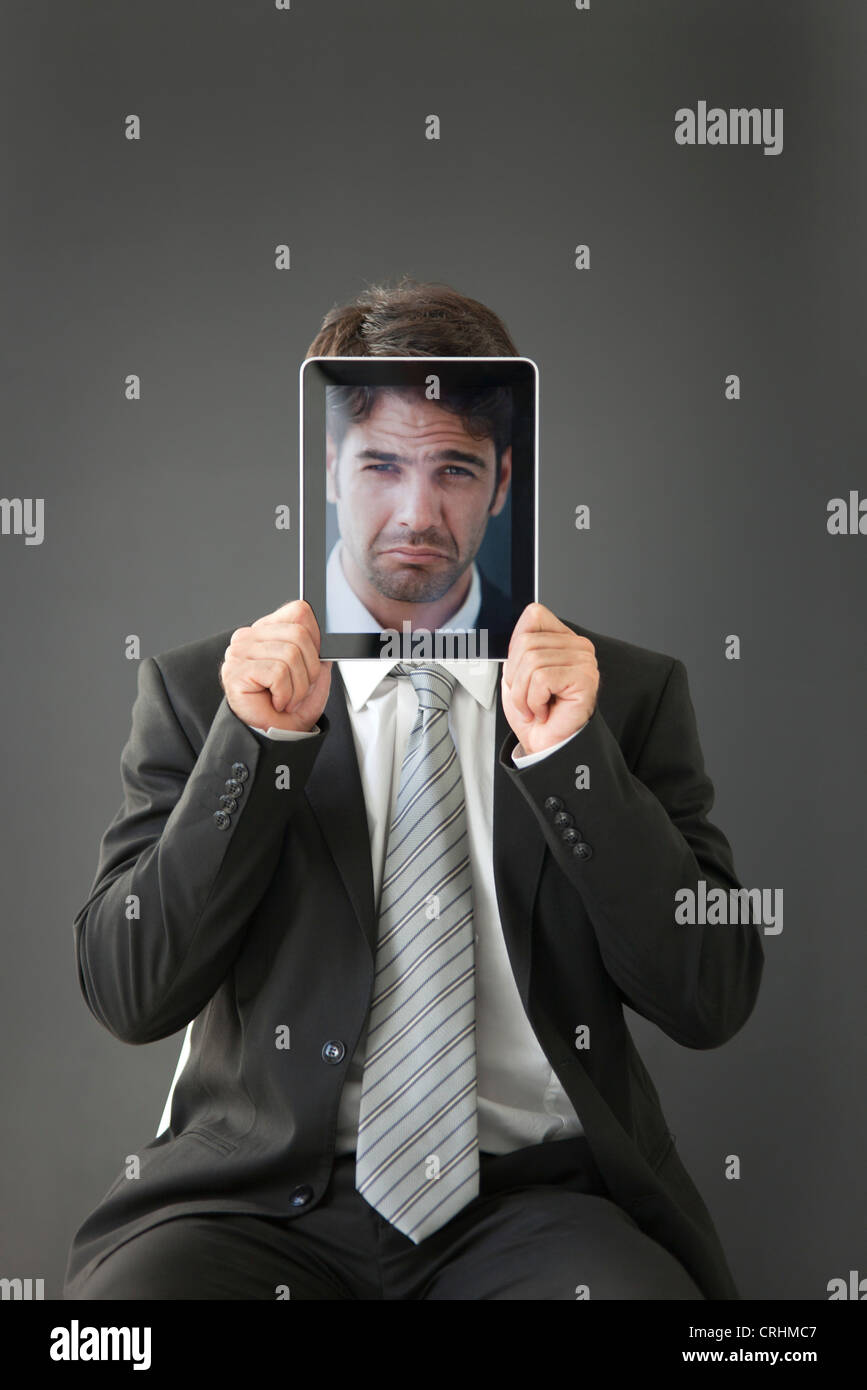 Man holding fronçant photographie en face de son visage Photo Stock