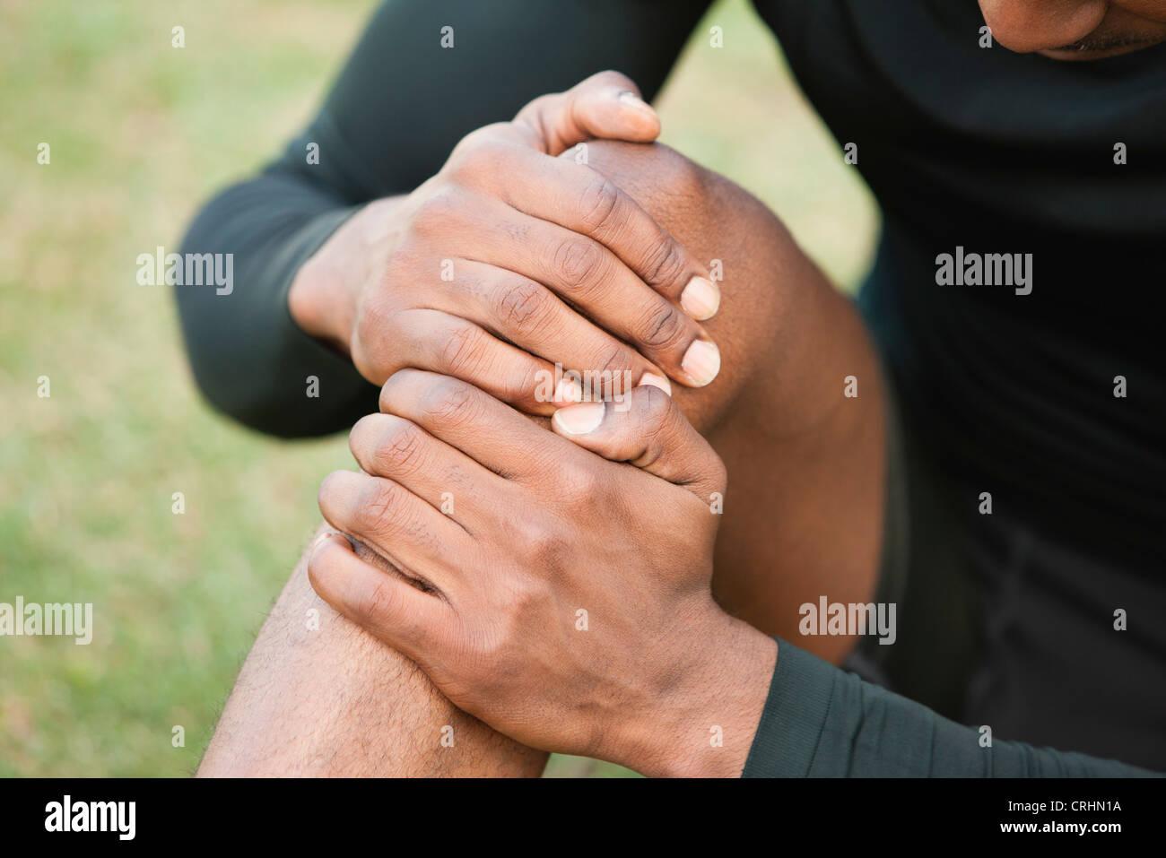 Man holding genou blessé, cropped Photo Stock