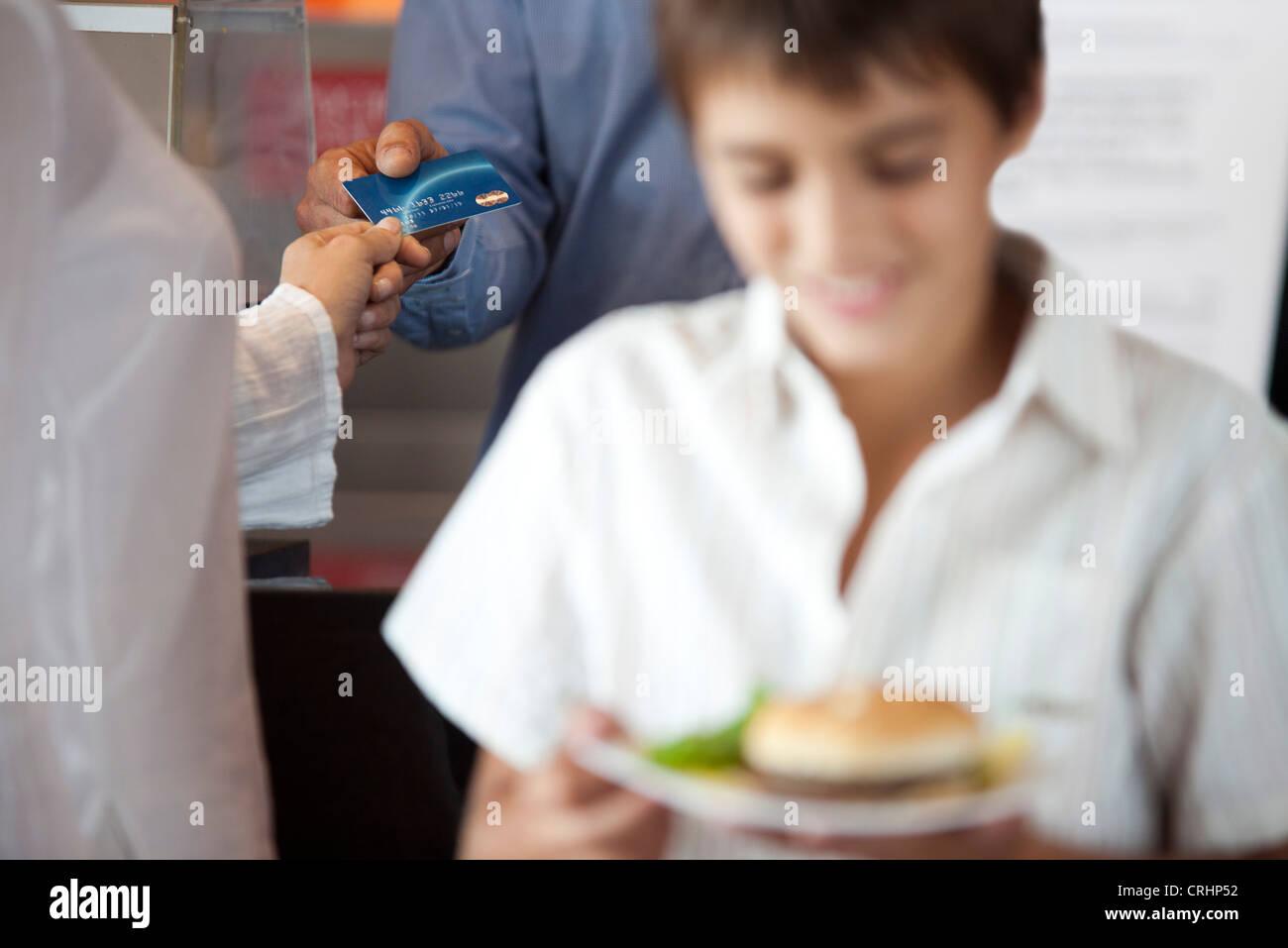 Femme de payer à l'achat avec carte de crédit, boy carrying assiette de nourriture en premier plan Photo Stock