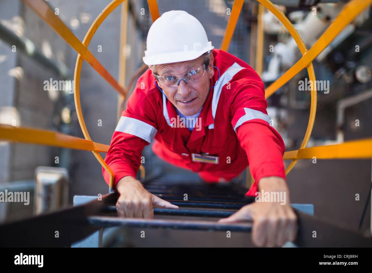 Worker climbing ladder à la raffinerie de pétrole Photo Stock