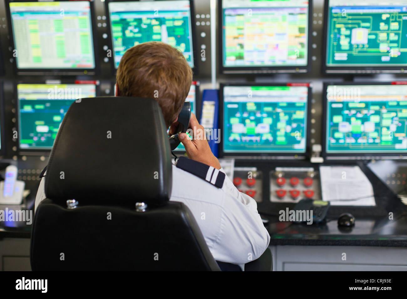L'homme travaillant en salle de contrôle de la sécurité Photo Stock