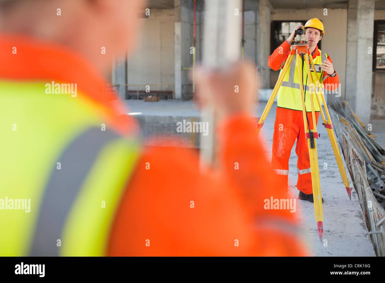 Travailleurs utilisant des engins sur le site Photo Stock