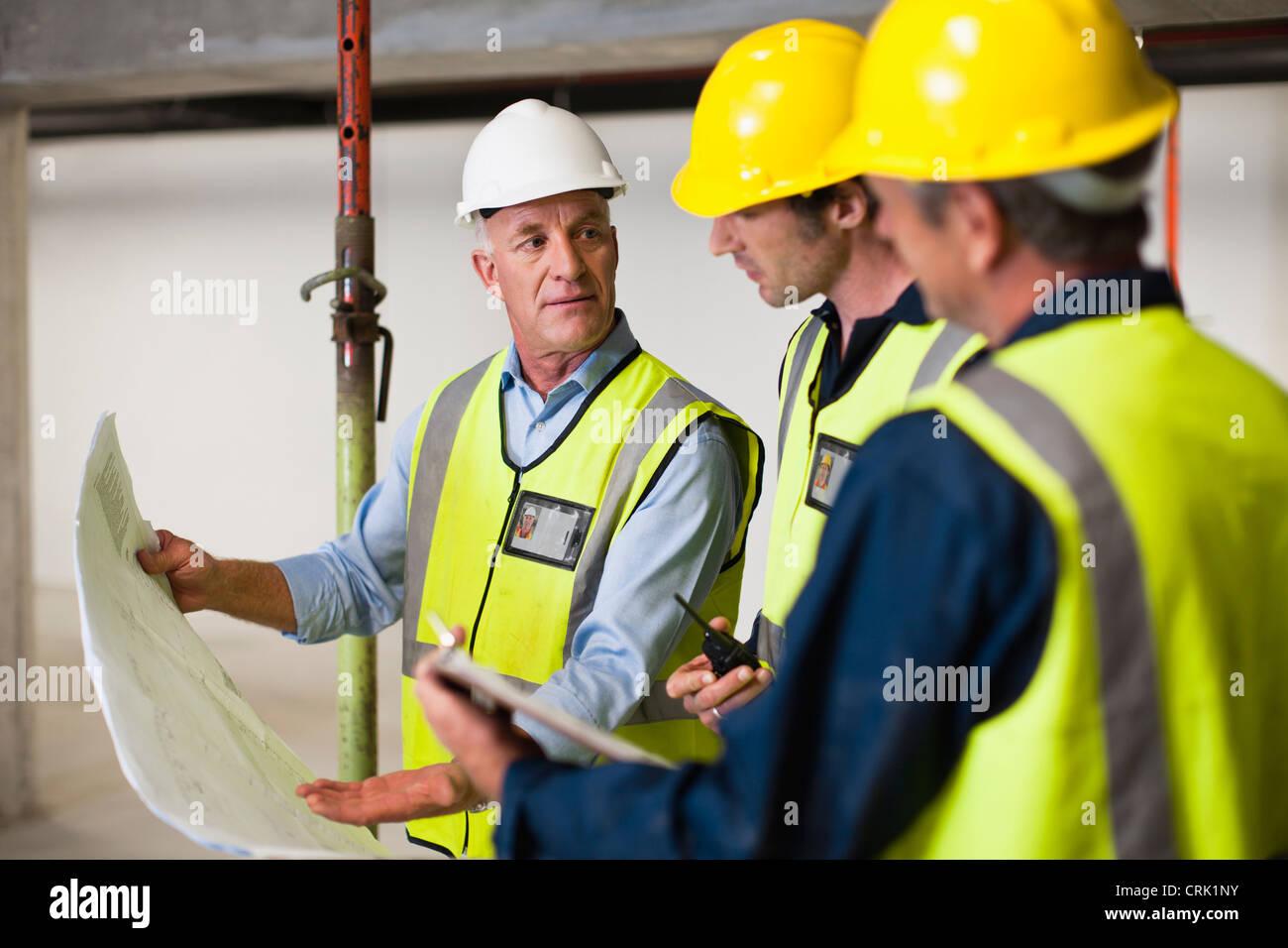 La lecture de bleus les travailleurs sur place Photo Stock