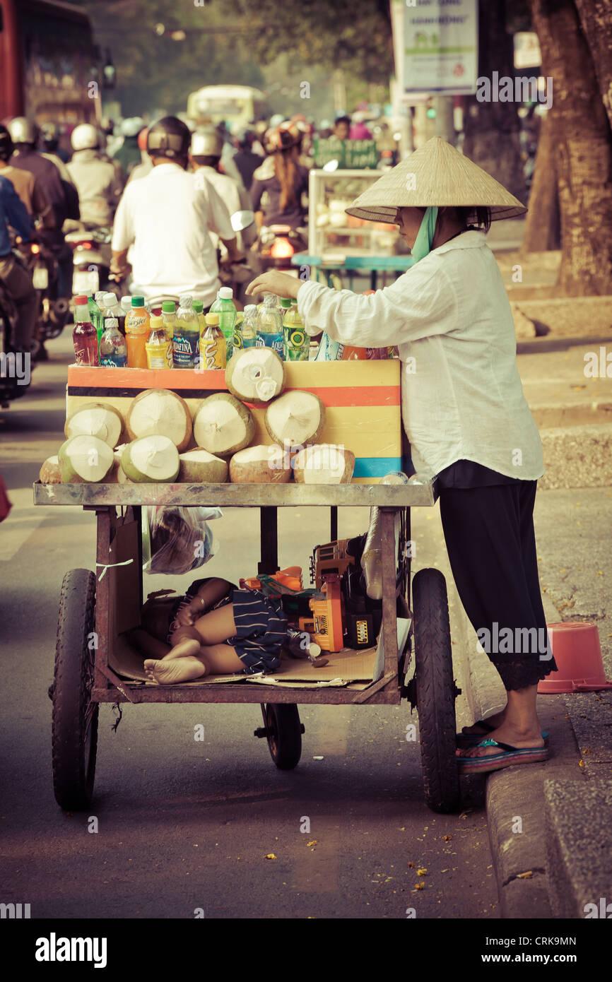 Vendeur de noix de coco dans une rue de HCM Ville, Vietnam. Le côté drôle ici, c'est son enfant Photo Stock