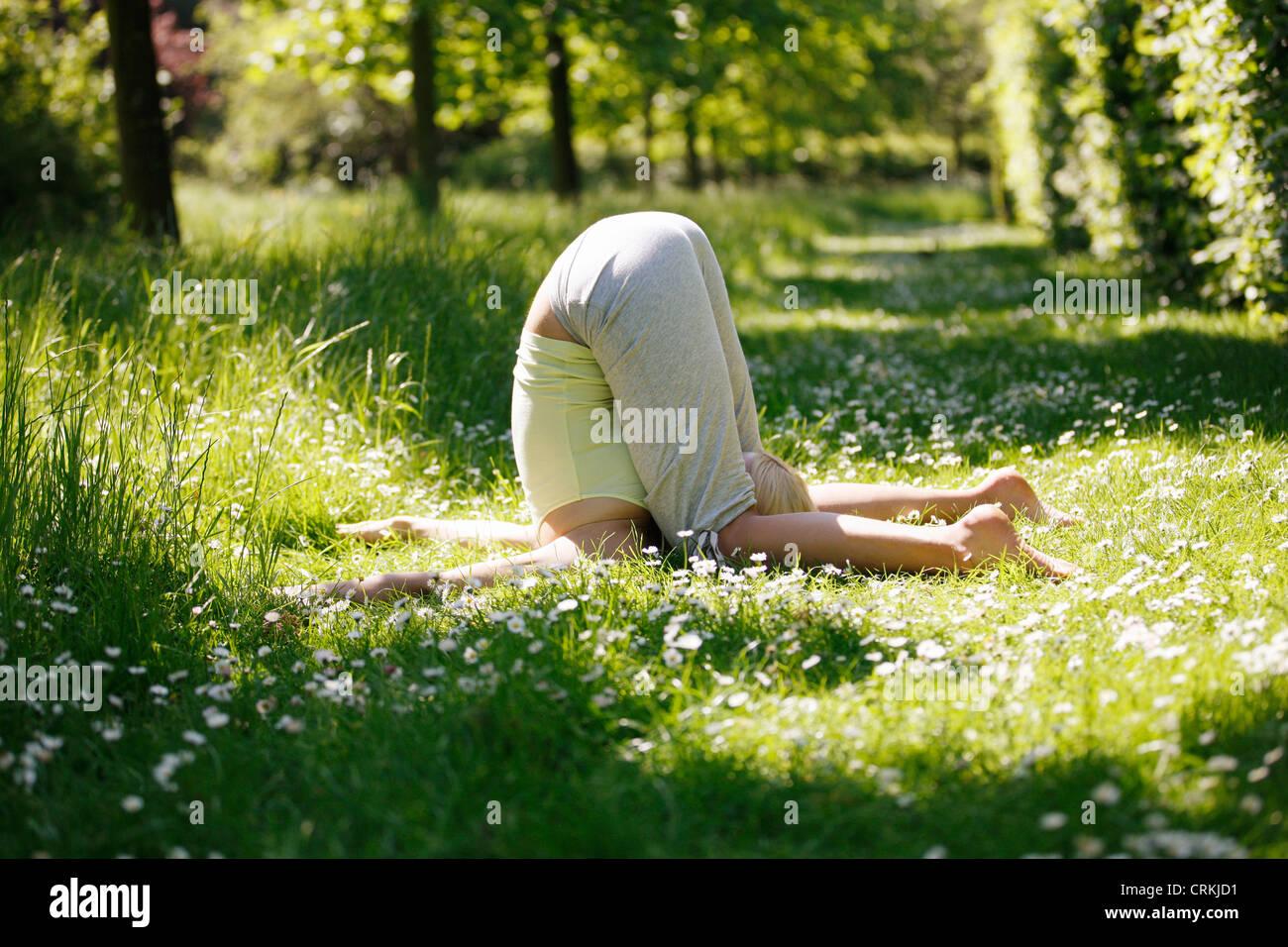 Une jeune femme pratiquant le yoga à l'extérieur, la pression de l'oreille poser Photo Stock