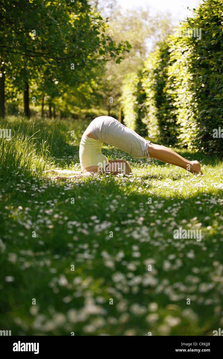 Une jeune femme pratiquant le yoga à l'extérieur, pose de charrue Photo Stock