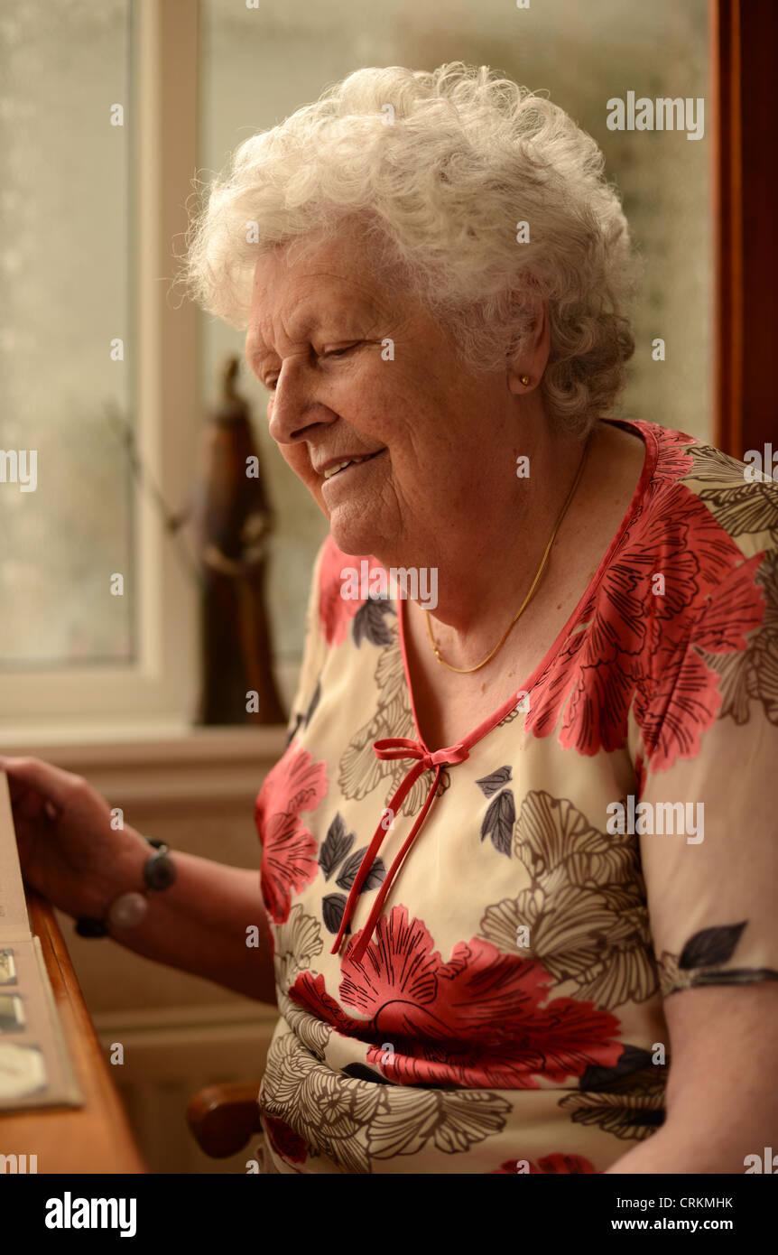 Une vieille dame à la recherche de photographies dans un album assis à table Photo Stock