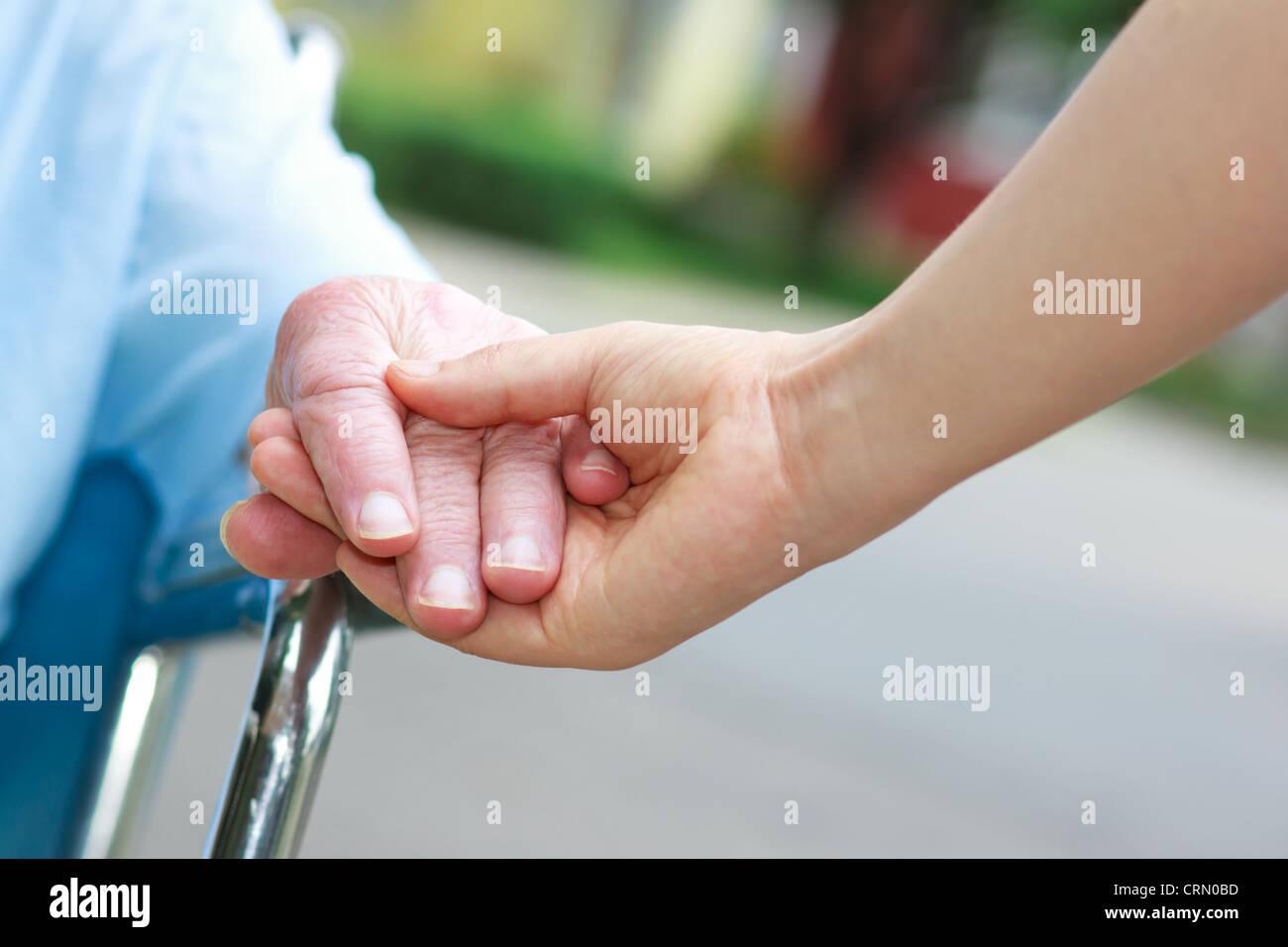 Les femmes âgées en tenant les mains en fauteuil roulant avec gardien Photo Stock