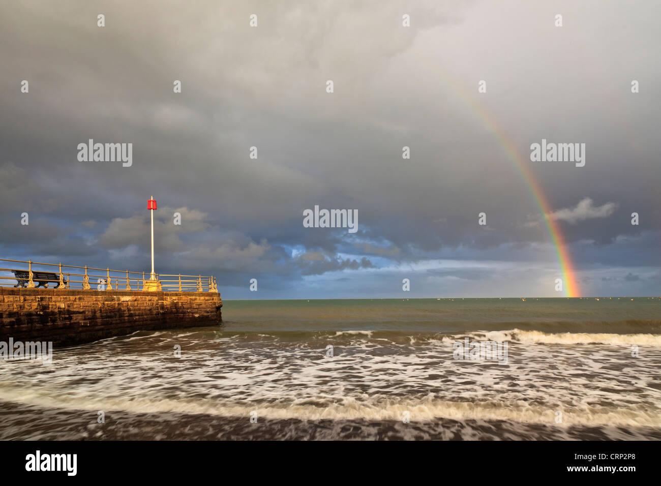 Arc-en-ciel sur la mer à Swanage avec la Jetée Banjo au premier plan. Photo Stock