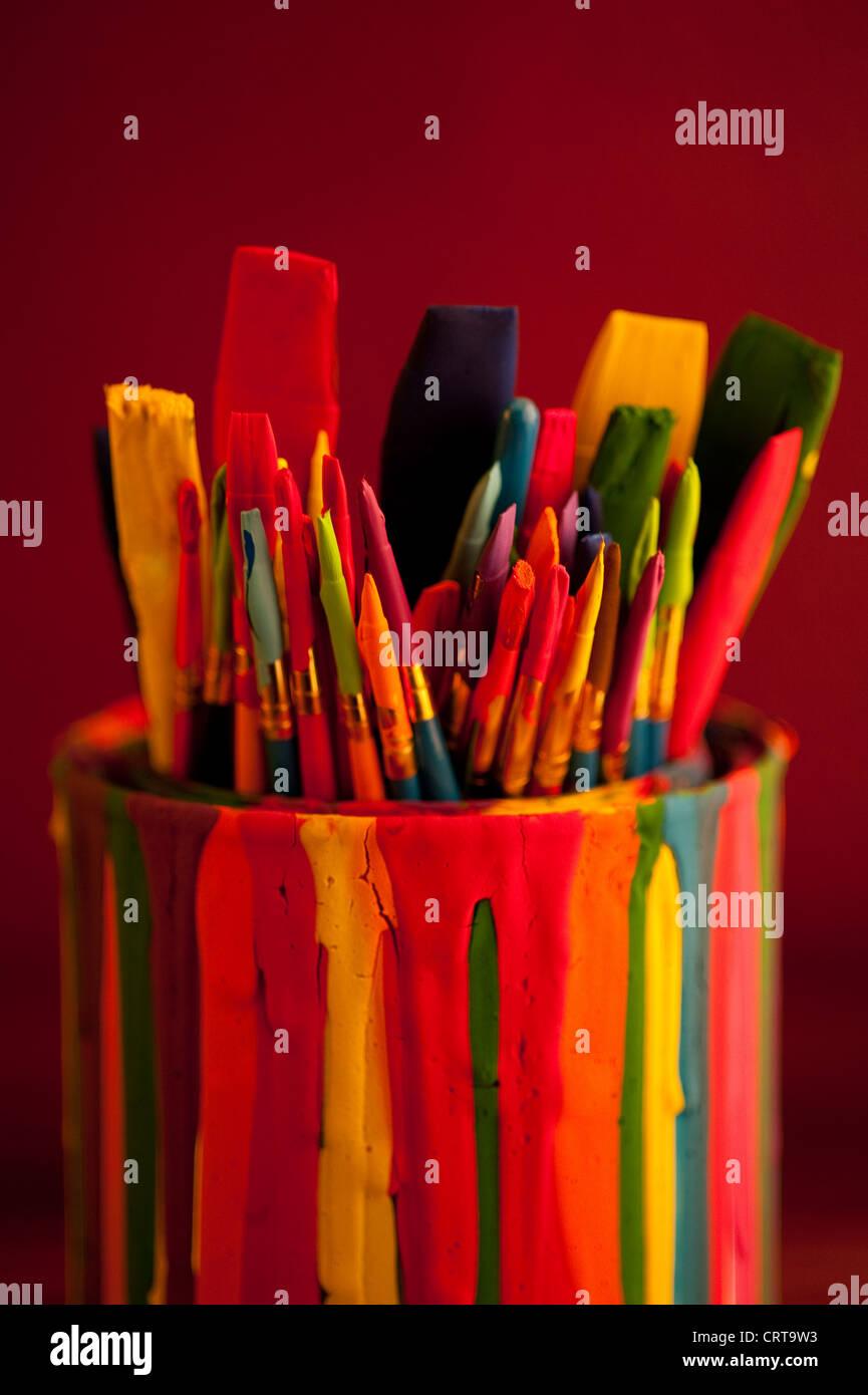 Pinceaux multicolores dans un pot recouvert de gouttes de peinture Photo Stock