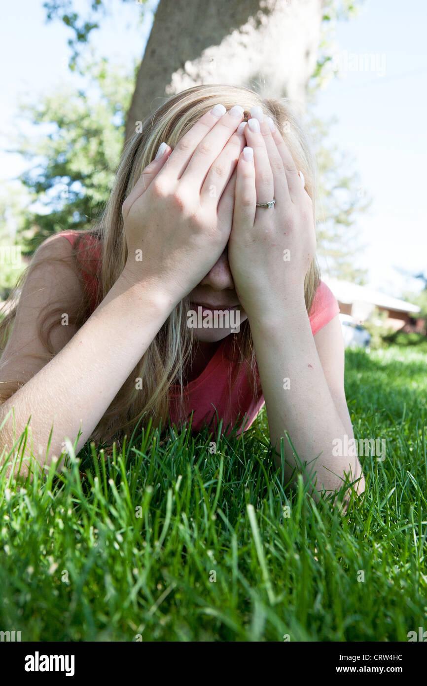 Fille de 13 ans humilié lui couvre le visage avec ses mains à l'extérieur. Photo Stock