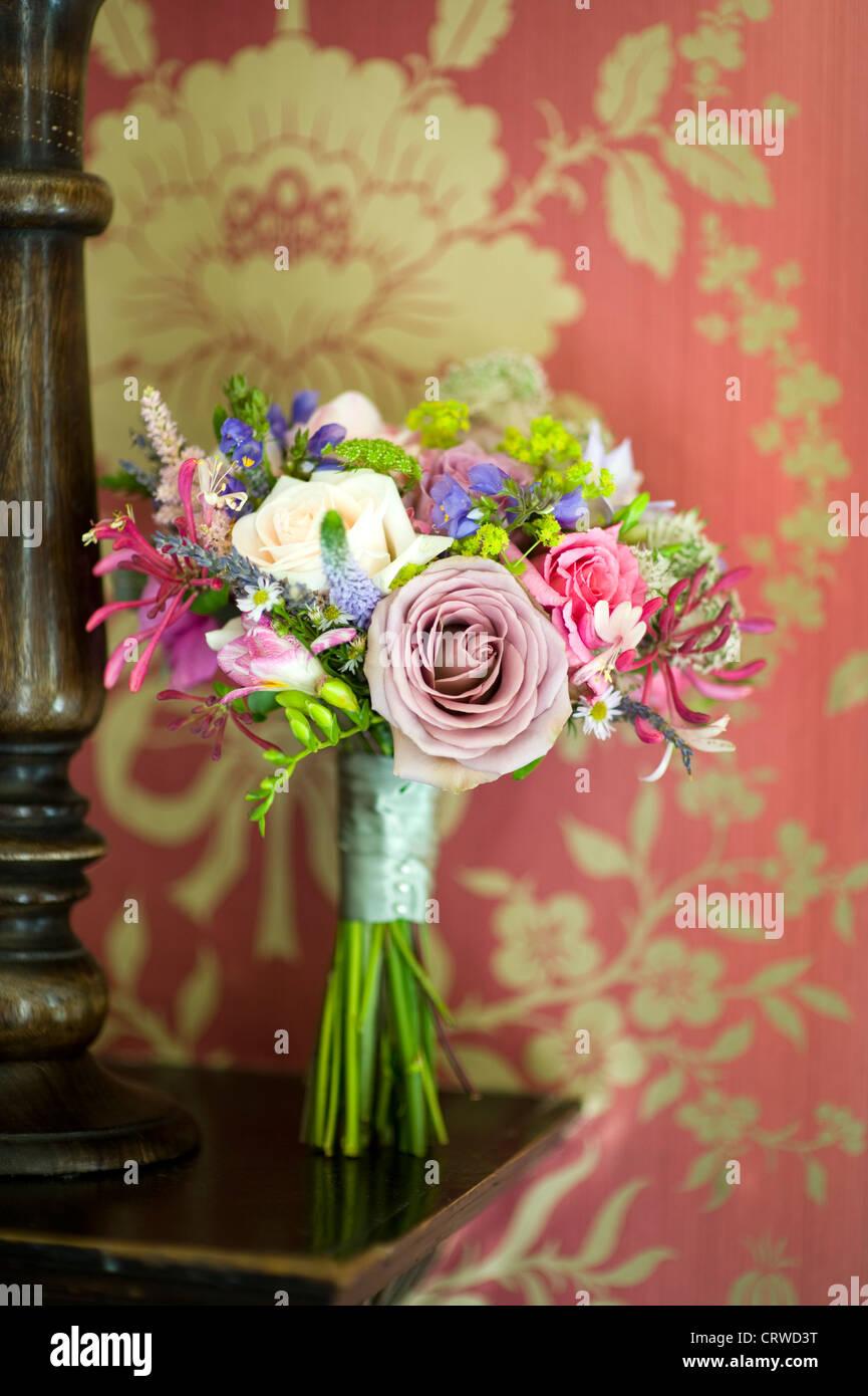 Bouquet de mariage sur un plateau en bois avec du papier peint à motifs vintage Photo Stock