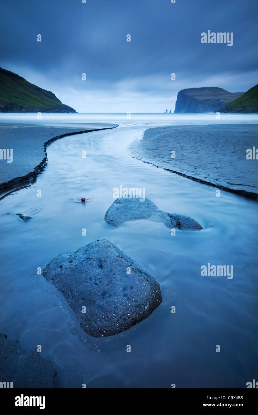 Un ruisseau se jette dans la mer à Tjornuvik sur l'île de Streymoy dans les îles Féroé. Photo Stock