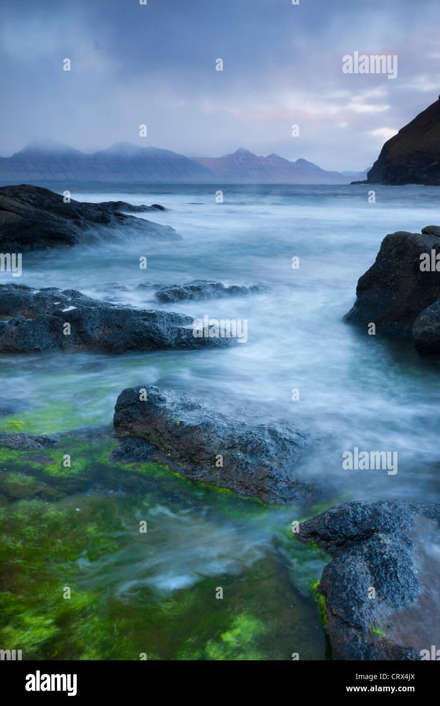 En regardant vers l'île de Kalsoy depuis les rives rocheuses de mais confortables et disposent, Eysturoy, Photo Stock
