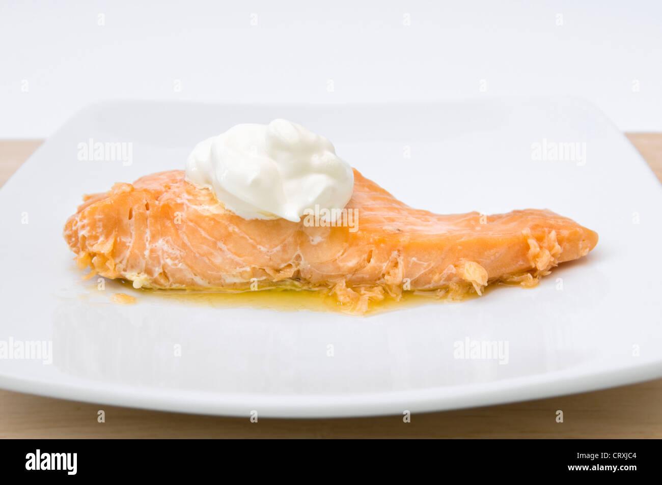 Le saumon cuit avec cuillerée de crème fraîche et de beurre fondu on white plate Photo Stock