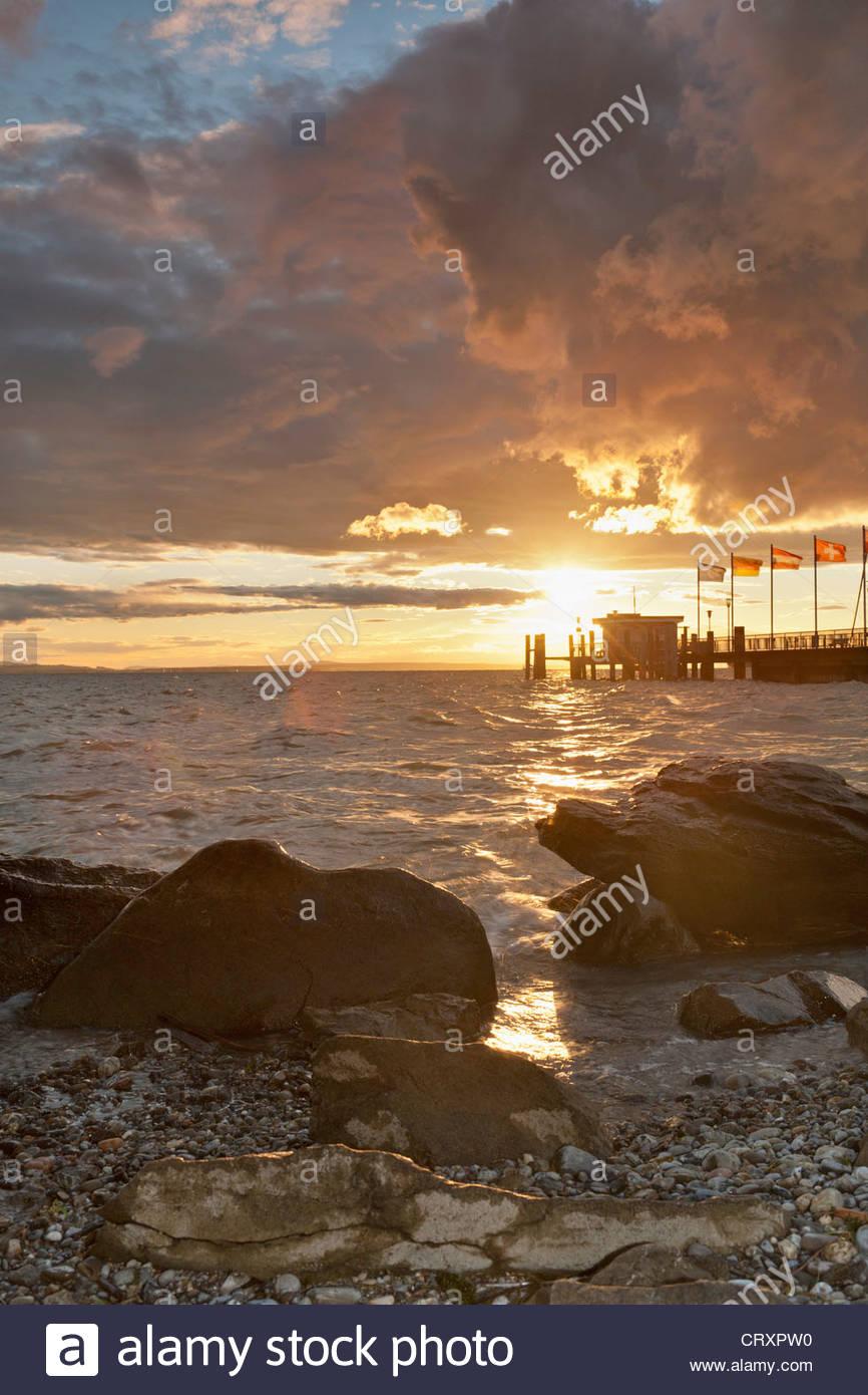 Allemagne, Nonnenhorn, vue sur le lac et les rochers de la jetée au coucher du soleil Photo Stock