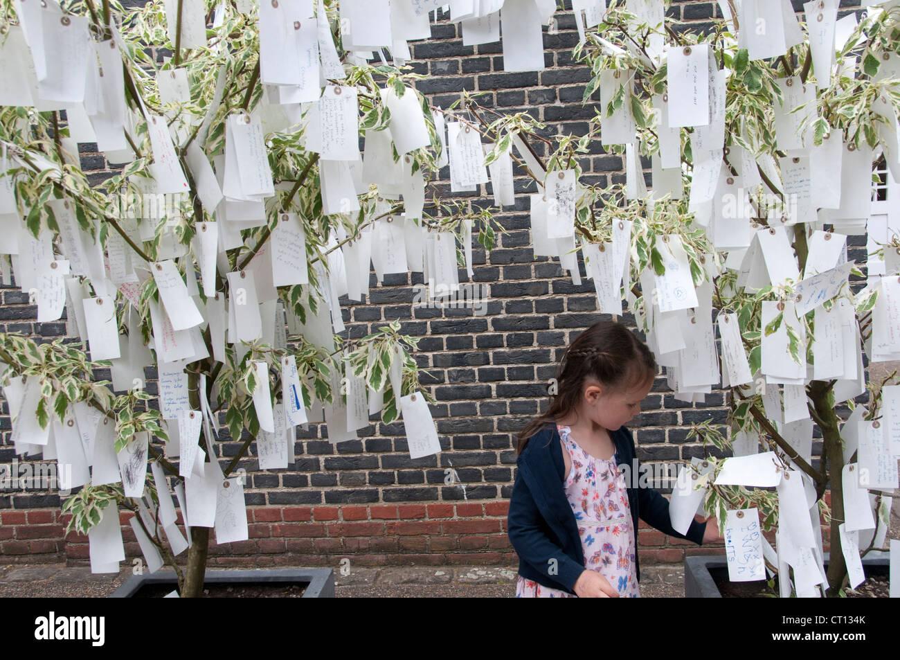 Serpentine Gallery - arbre des désirs par Yoko Ono - enfant l'examen des étiquettes avec des souhaits écrits sur eux Banque D'Images