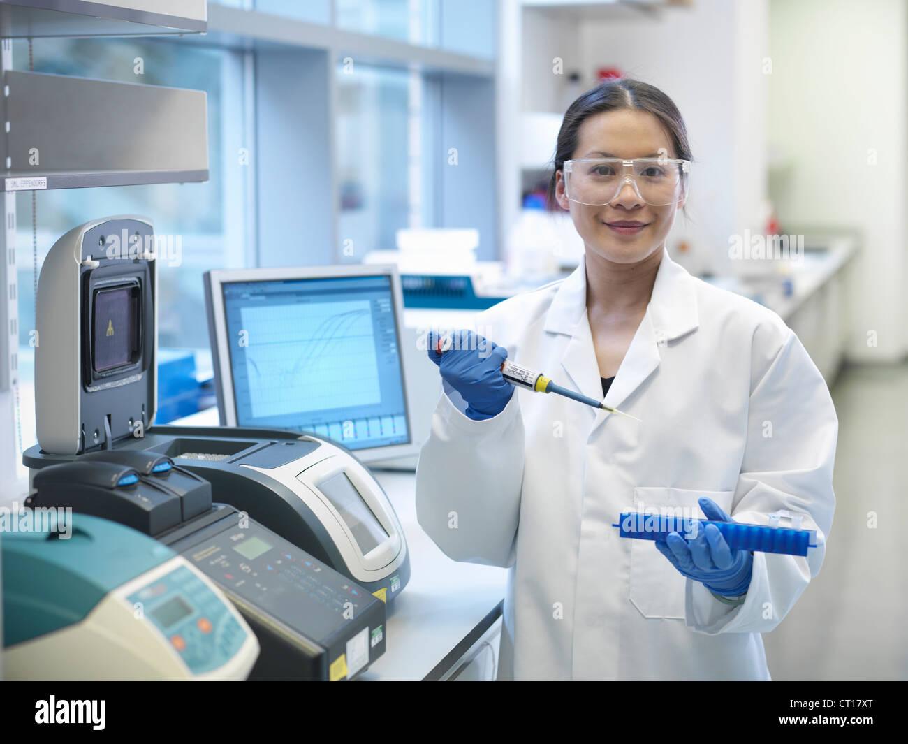 La tuyauterie des scientifiques dans des tubes de liquide Photo Stock