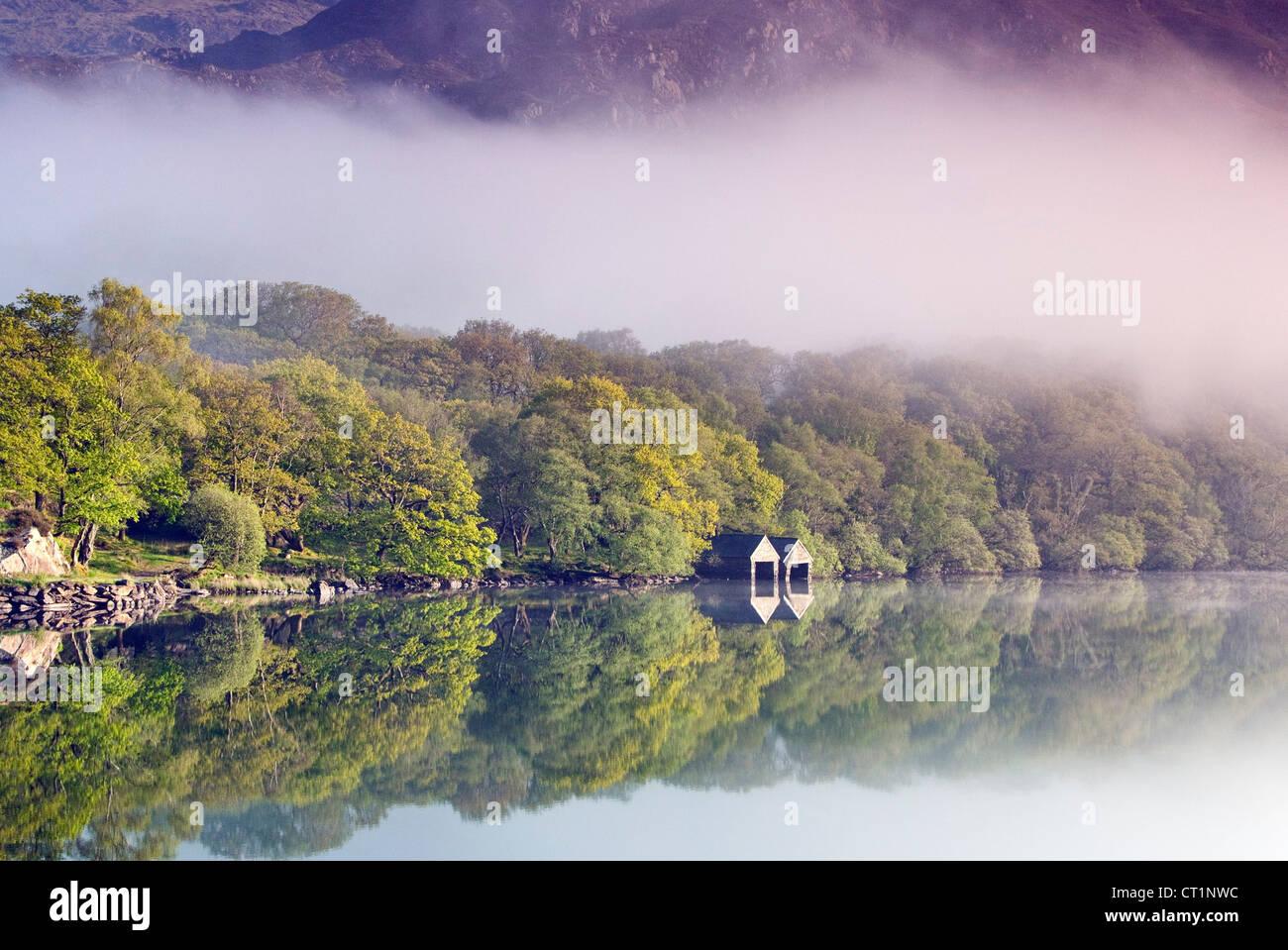 Bateaux sur la rive occidentale du nord bordée d'un lac brumeux Llyn Dinas dans la vallée au nord Photo Stock