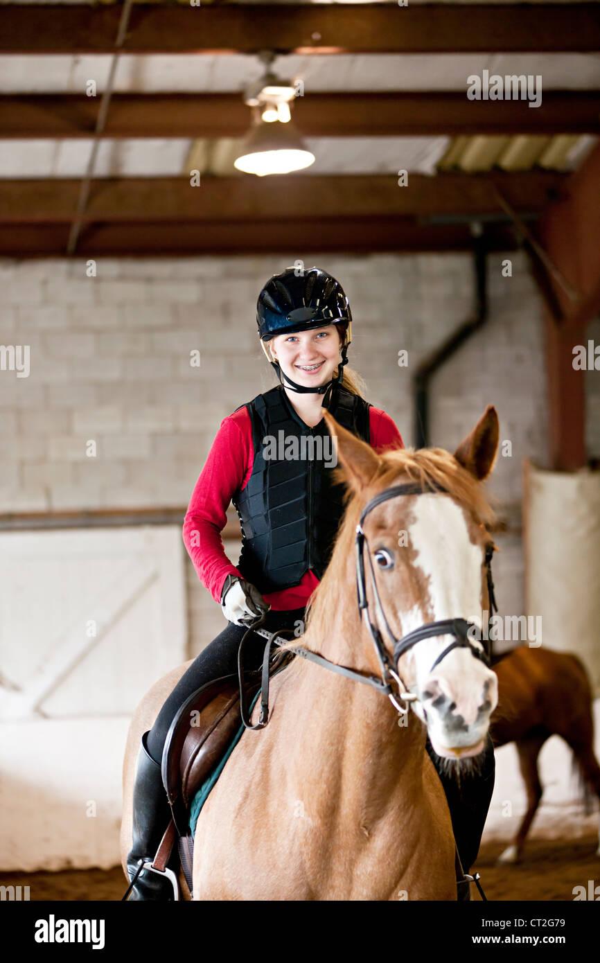 Adolescente à cheval portant casque et gilet de sécurité en indoor arena Photo Stock