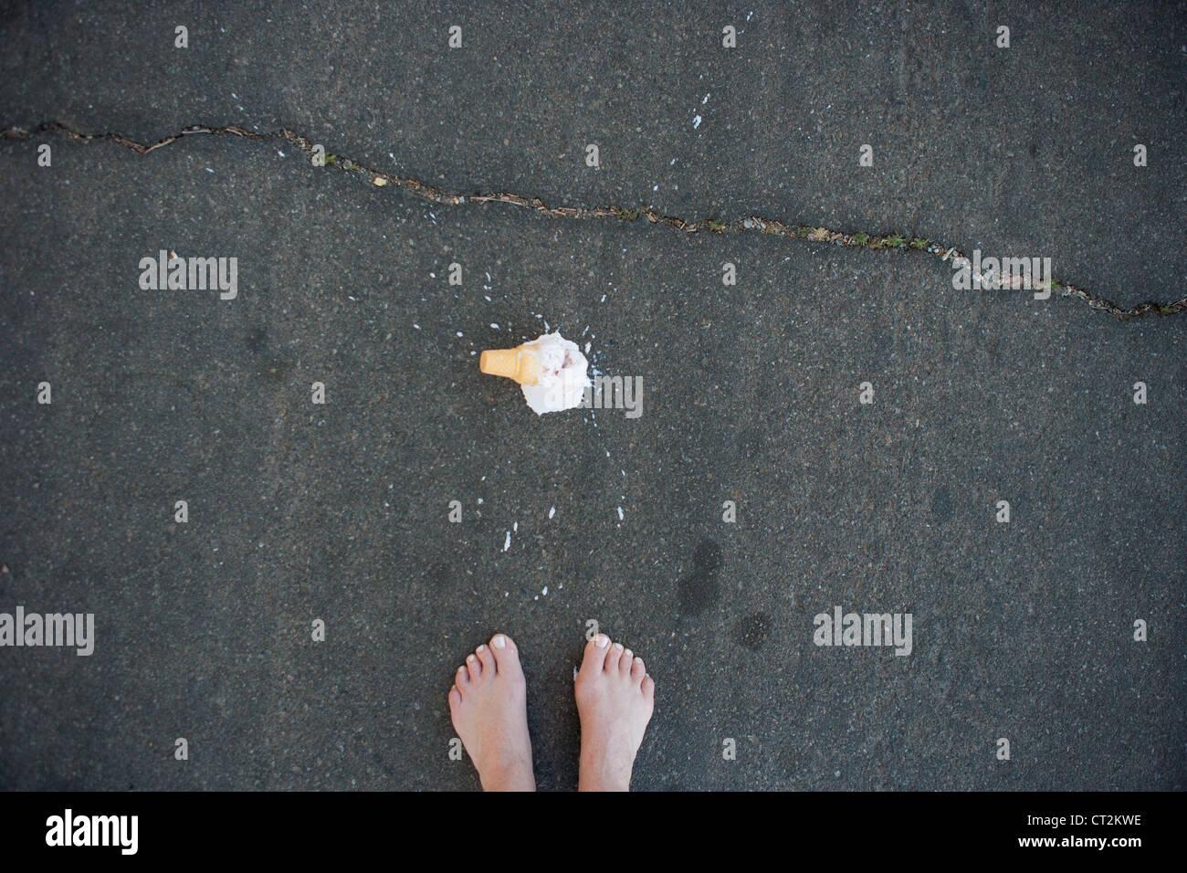 La plante des pieds avec ice cream cone a chuté sur la chaussée. Photo Stock