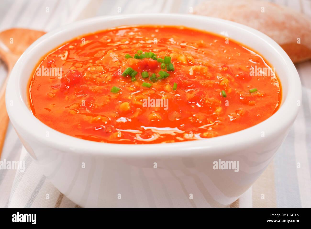 Un bol de soupe aux tomates et lentilles garmished avec la ciboulette. Photo Stock
