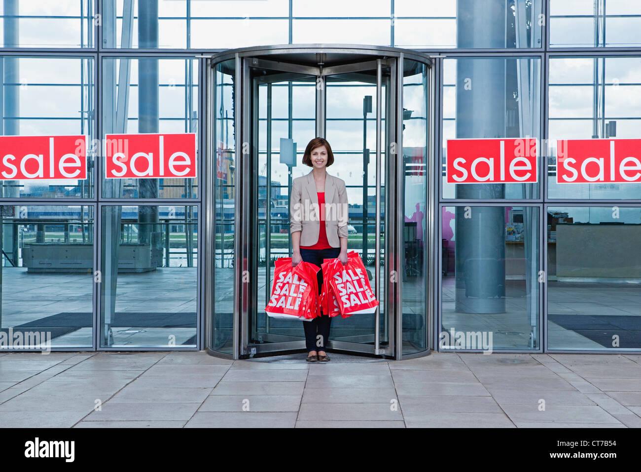 Femme en porte avec des sacs boutique vente Photo Stock