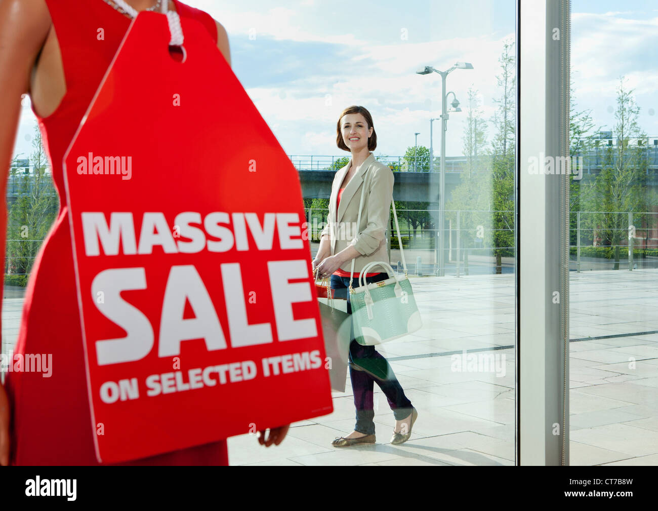Woman looking at sale sign in shop window Photo Stock