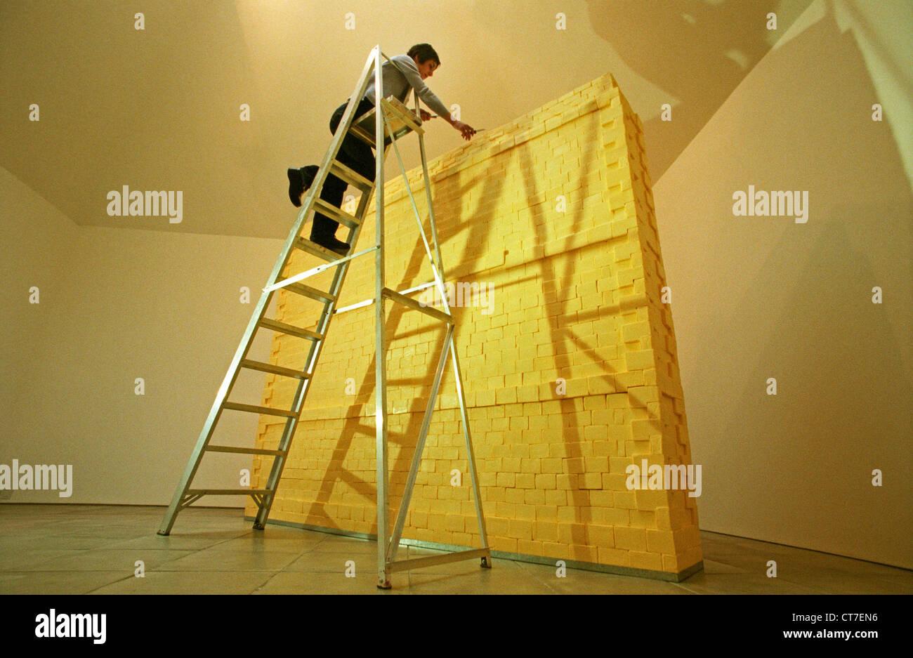 Femme artiste sur l'échelle, la sculpture un mur fait entièrement de beurre. Il pesait trois quarts Photo Stock