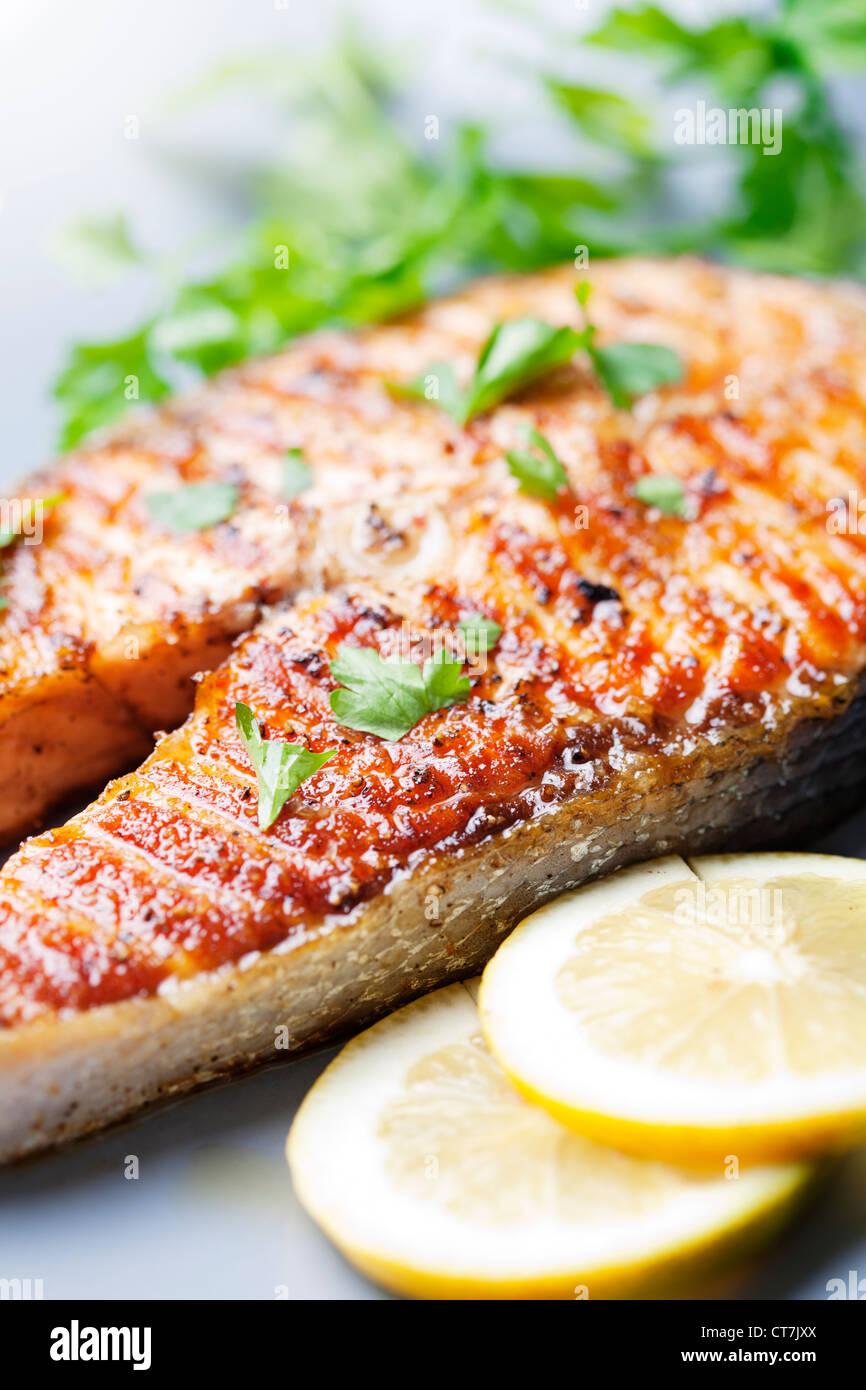 Pavé de saumon grillé croustillant avec les tomates cerise et le persil Photo Stock