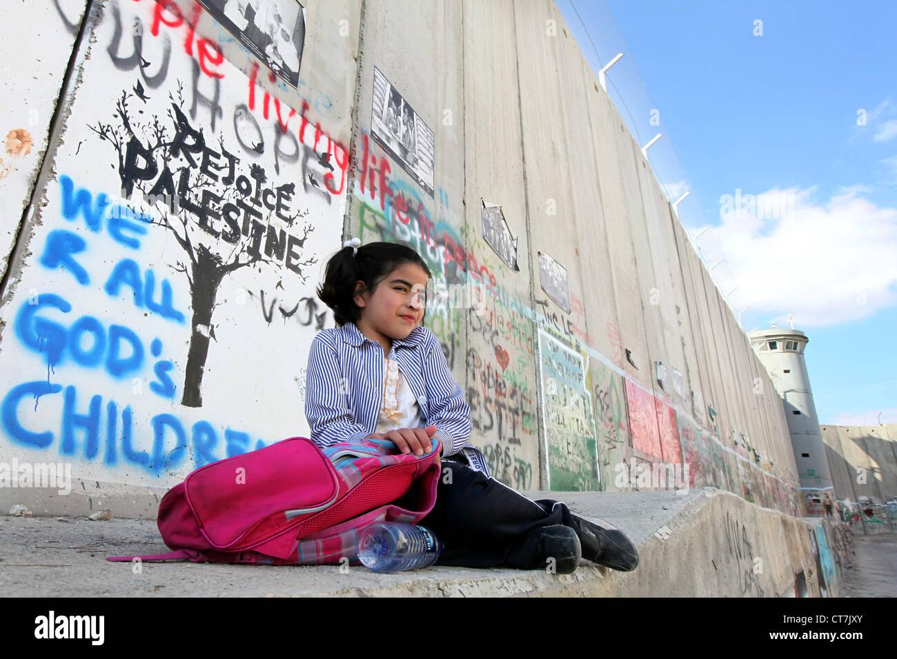 Fille assise sur le mur de séparation israélien. Ce mur sépare les terres palestiniennes en Cisjordanie Photo Stock