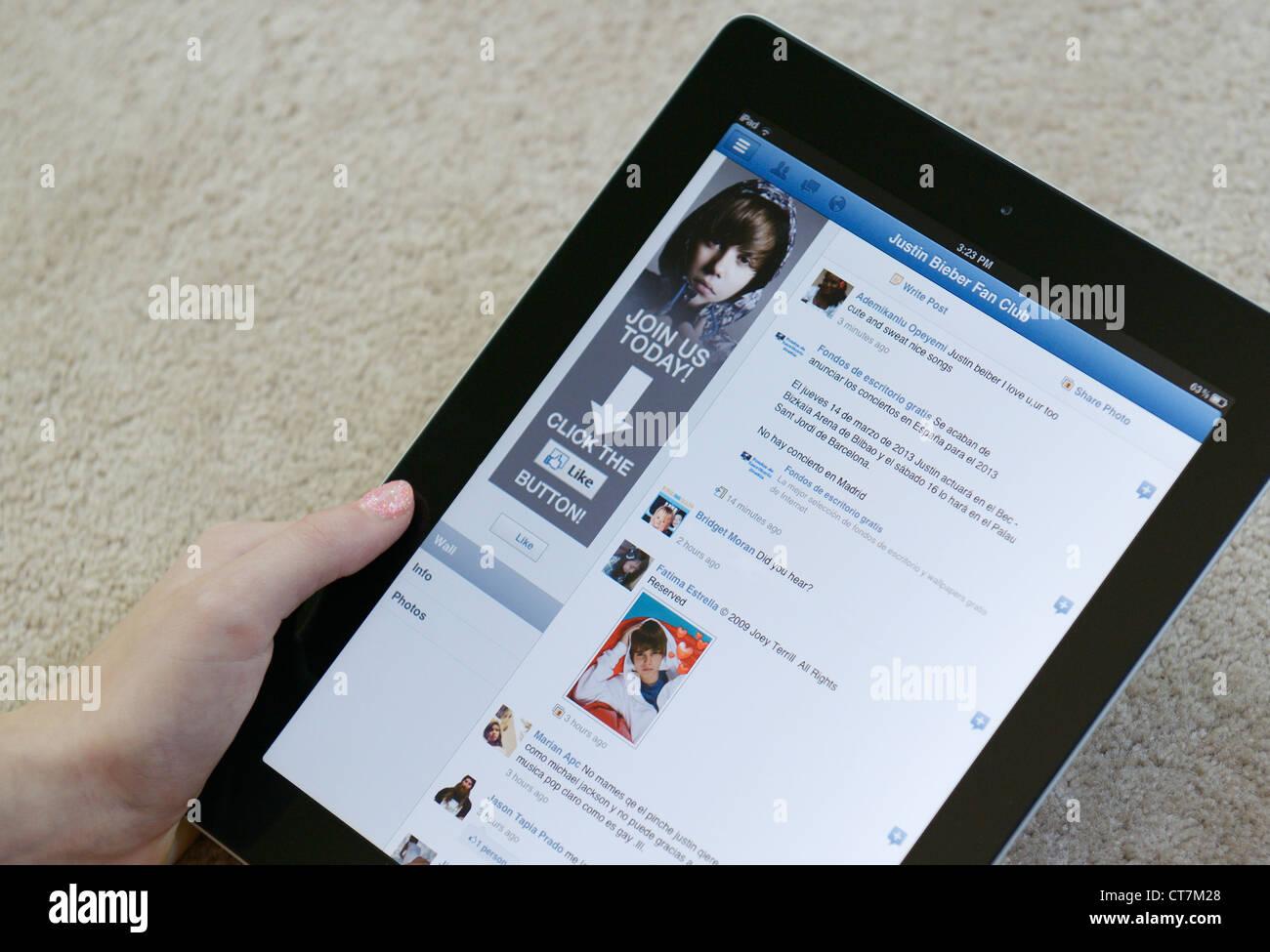Girl holding un iPAD à la recherche et le Justin Bieber fanclub page sur Facebook Photo Stock